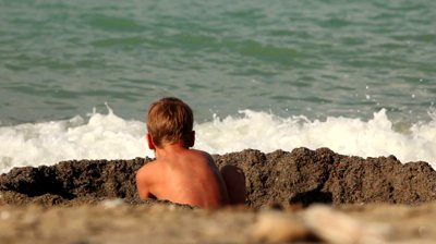 Stock-footage-the-boy-digs-a-hole-in-the-sand-in-front-of-the-sea-water
